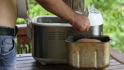 man takes container out of breadmaker and puts on table
