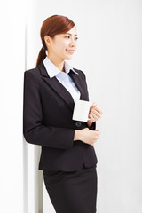 young businesswoman leaning against white wall in office