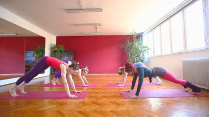 Women doing yoga class in hall