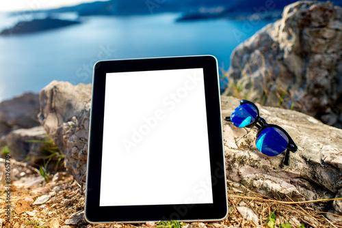 Leinwanddruck Bild Digital tablet with sunglasses on the mountain