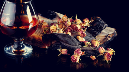 Rose petals on books and bottle of wine.