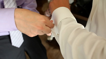 Two mens attaching cuff links a moment before wedding