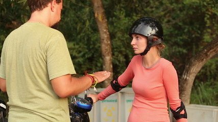 girl in motor helmet sits on scooter and listens to bearded guy