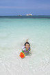 Cheerful little girl swimming at beach