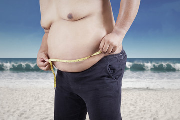 Obese person measuring his belly