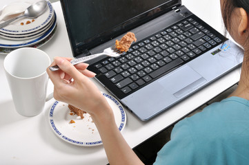 have lunch among stack of dirty plates while busy and using lapt