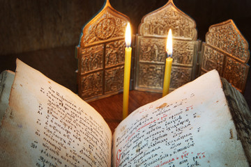 Religious still life with open ancient book and burning candles