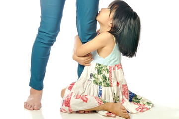 little asian girl looking up and holding her mother leg