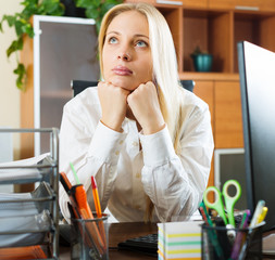 woman in white dreaming at office desk