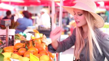 Blonde girl at the market picking lemons