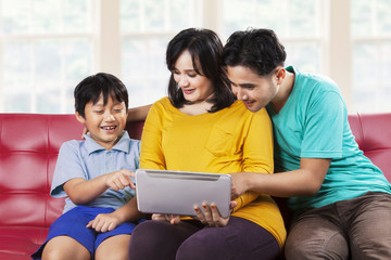 Two parents and their son using tablet