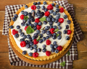 Cake with  fresh raspberries and blueberries.