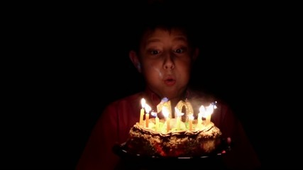The birthday boy blows out the candles on cake slow motion