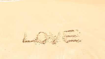 Ocean wave approaching word love written in sand on beach