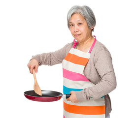 Asian housewife frying with skillet