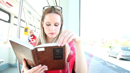 Beautiful woman riding tram, while reading book