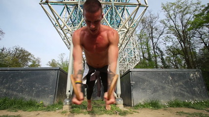 Close up of muscular man doing push ups with gymnastics rings