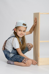 Little girl in overalls collector of furniture turn