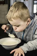 boy eats hot porridge
