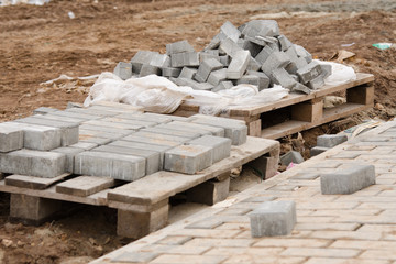 Elements of paving slabs lying on ground near sidewalk
