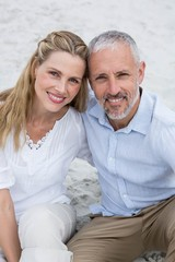 Happy couple sitting on the sand and looking at the camera