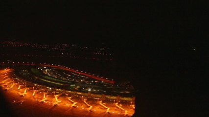 View of Doha airport at night seen from the plane window.