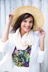 Smiling beautiful brunette wearing straw hat