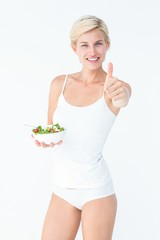 Beautiful fit woman holding a bowl of salad with thumbs up
