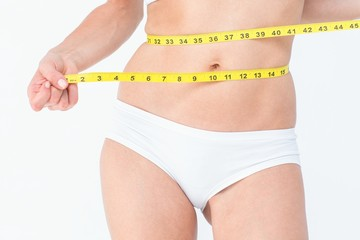 Attractive woman measuring her belly