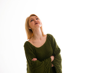 Woman in a sweater looking up with interest  on a white backgrou