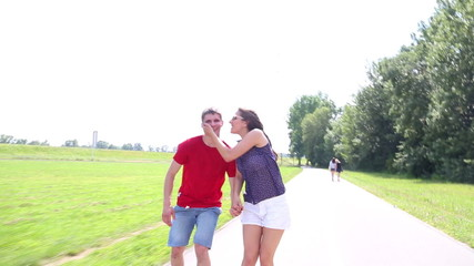 Happy young couple rollerblading on a wonderful sunny day in park, holding each other