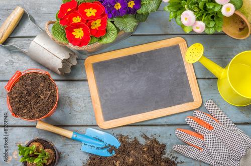 Leere Tafel auf Pflanztisch mit Gartenutensilien