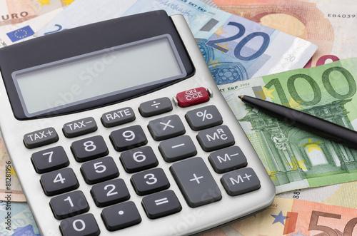 Leinwandbild Motiv Taschenrechner mit Geldscheinen