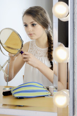 Model schminkt sich vor Schminkspiegel