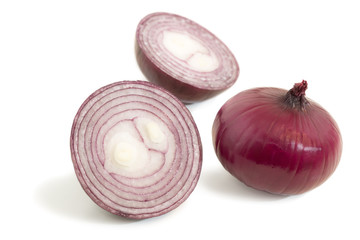 Closeup of a halved and a whole red onions isolated on white