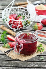 Homemade delicious strawberry jam on a rustic wooden table