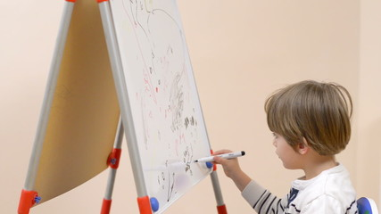 Cute boy drawing at kindergarten on a white board