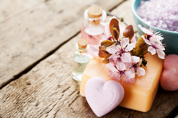 Spa setting with soap, bath salt, essential oils and flowers