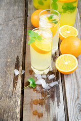 Cold orange soda in a glass on a wooden background