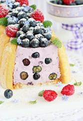 Homemade yogurt mousse cake ( charlotte ) with fresh berries.