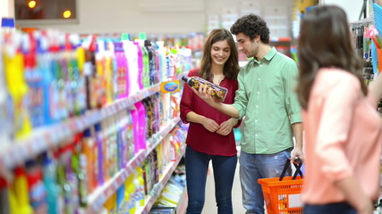 Customers choosing cleaning products in supermarket