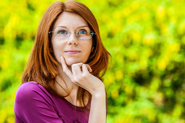 red-haired smiling young woman with glasses reflects