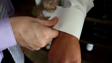 Two men attaching cuff links a moment before wedding