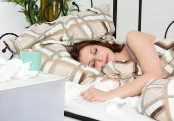 Erkältete Frau ist im Bett eingeschlafen
