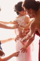 Bridesmaids hands helping the bride with her wedding dress