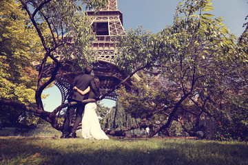 Bride and groom sitting on a tree near Eiffel Tower