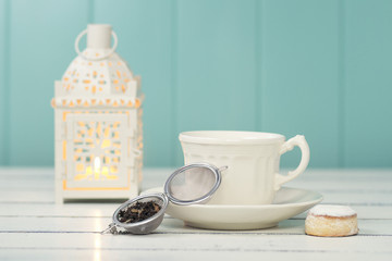 A candle, a cup, a tea infuser and a shortbread. Vintage