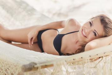 Portrait of a sexy girl in a bikini lying on a hammock