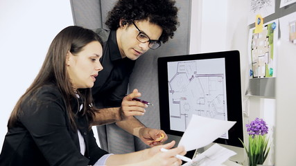 Two architects at work in office on house project.