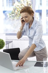 Young woman on mobile in office